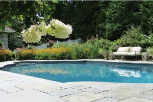 Earthscapes beautiful landscape design of a backyard, lawn, and pool area in Darien, CT